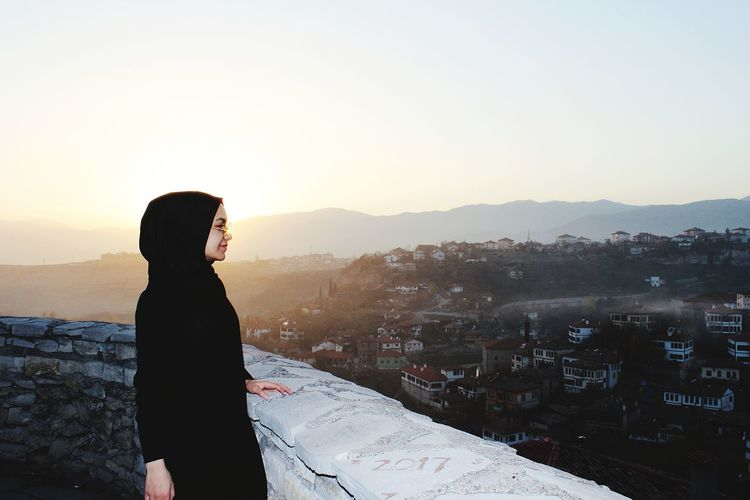 Woman Wearing Hijab Standing By Retaining Wall Against Sky