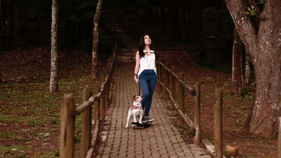 Full length of young woman and dog on skateboard in park