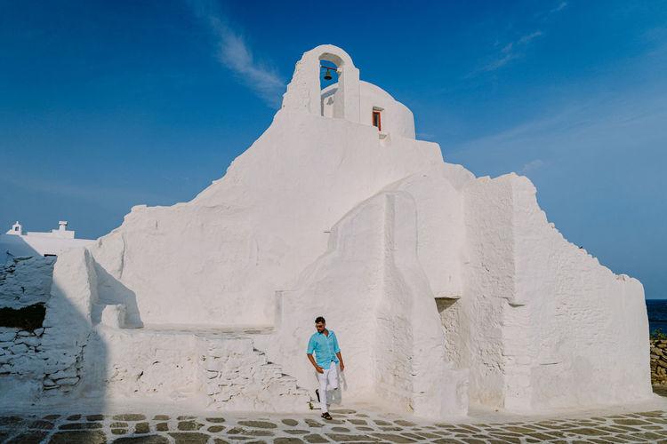 Full length of man standing outside temple against sky