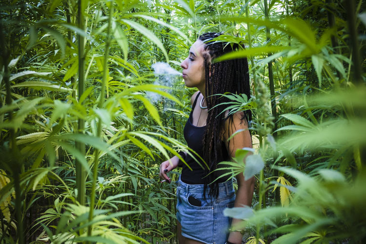 Young Woman Smoking Cigarette While Standing Amidst Plants