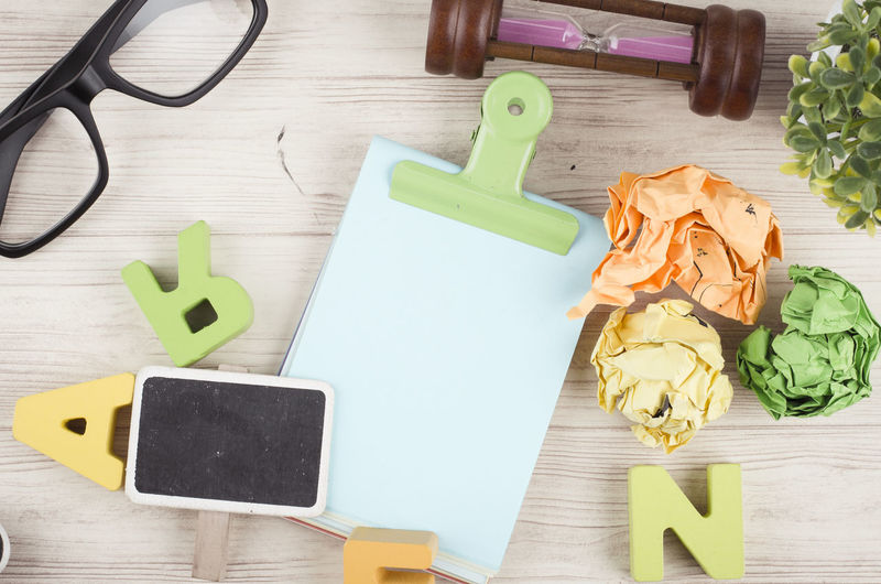 Flat lay or top view wooden office table desk with stationary. Table Still Life Wood - Material Indoors  High Angle View No People Yellow Directly Above Food And Drink Communication Food Close-up Paper Freshness Container Multi Colored Text Green Color Cutting Board Large Group Of Objects