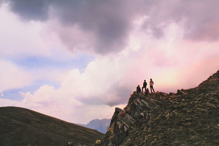 Low Angle View Of Hikers Standing On Cliff Against Cloudy Sky