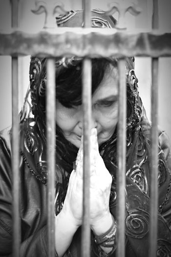 Woman Praying Seen Through Fence