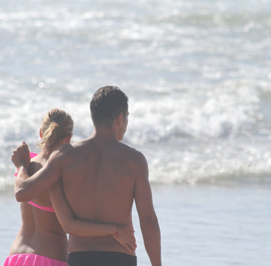 Rear view of couple walking at beach during sunny day