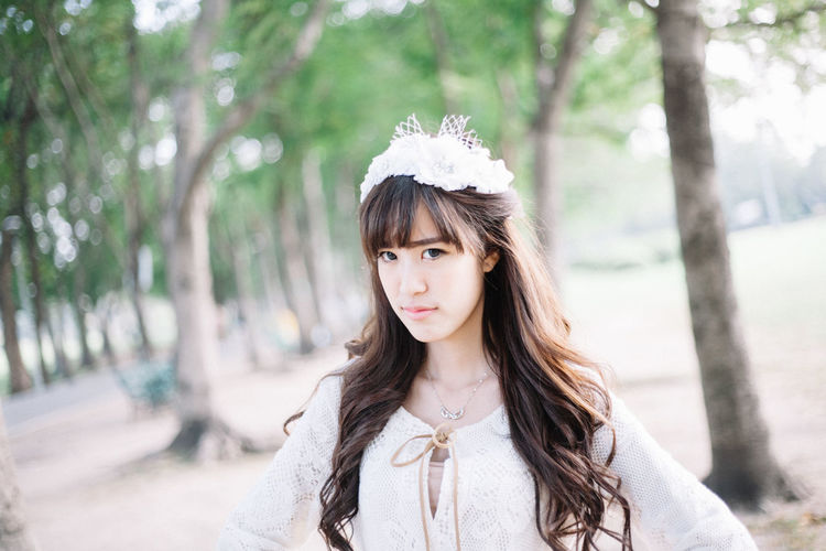 Portrait of woman wearing tiara while standing against trees