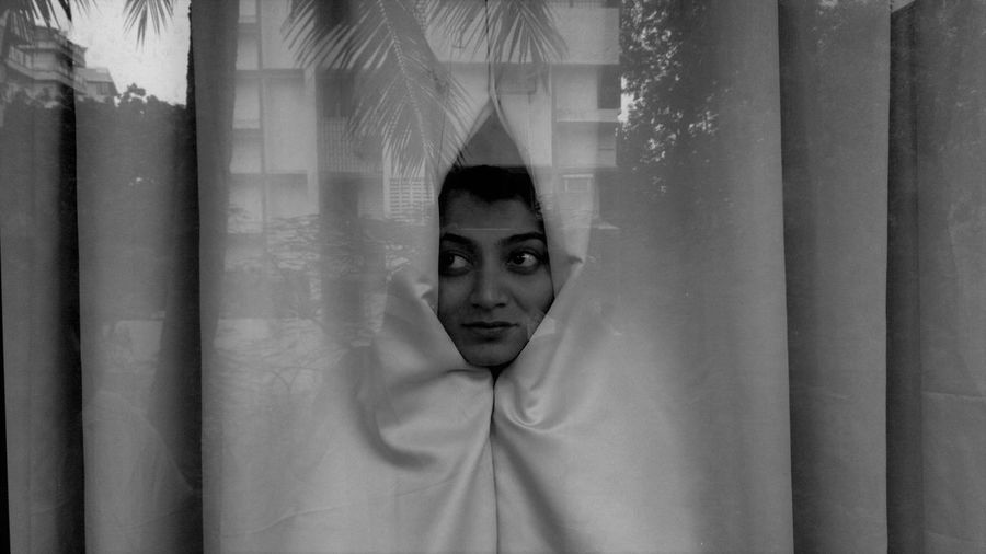 Portrait of woman wrapped in curtain
