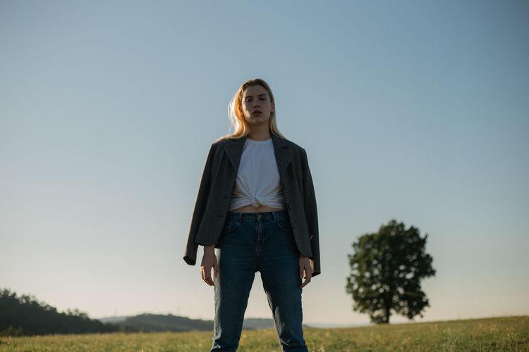 Portrait of woman standing on field against sky