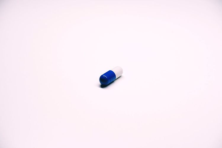 Medicine Pills Studio Shot Indoors  Copy Space White Background No People Single Object Still Life Close-up Simplicity Cut Out High Angle View White Color Two Objects Pill Healthcare And Medicine Dose Capsule Nutritional Supplement Blue