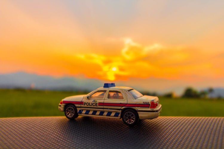 Toy car on field against sky during sunset