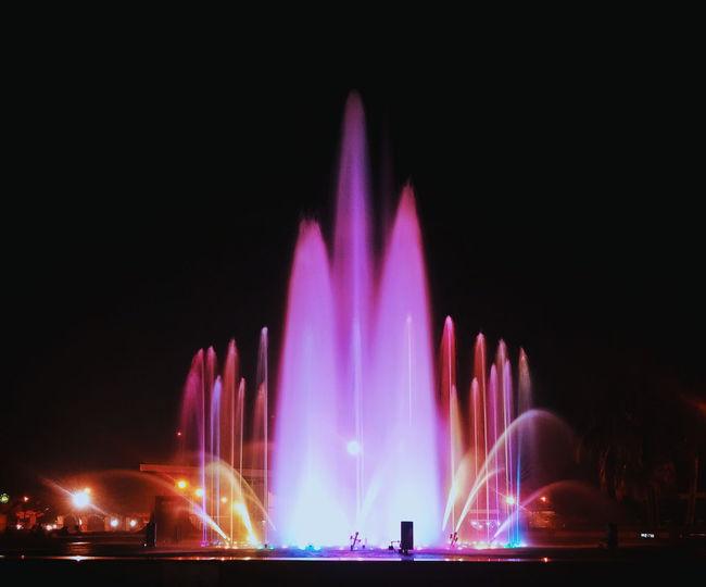 Illuminated fountain in city against sky at night