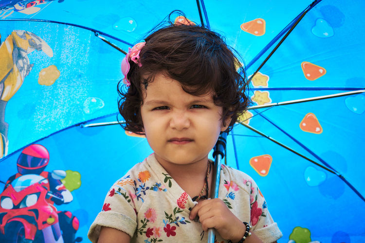 Portrait of cute girl making face while holding blue umbrella