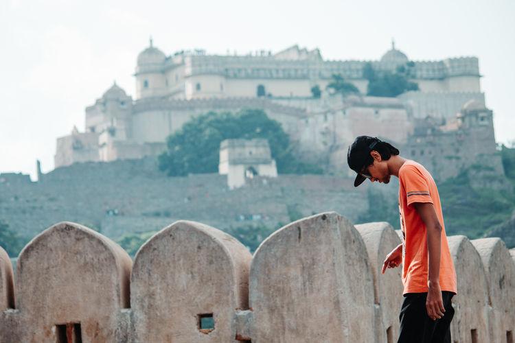 Full length of man standing outside temple against buildings