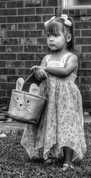 Cute girl standing against brick wall