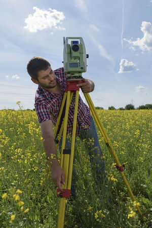 Land surveyor adjusting total station in a rapeseed field. Geodesy measurement Agriculture Industry Land Sunny Work Adjusting Beard Caucasian Day Engineer Equipment Field Geodesy Instrument Internet Location One Man Only Point Professional Occupation Rapeseed Surveyor Technology Tripod Wireless Technology Yellow