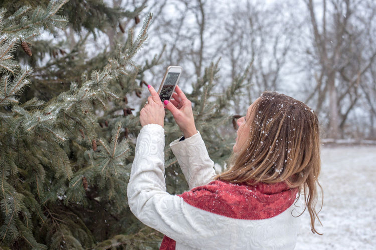 Woman holding mobile phone in snow