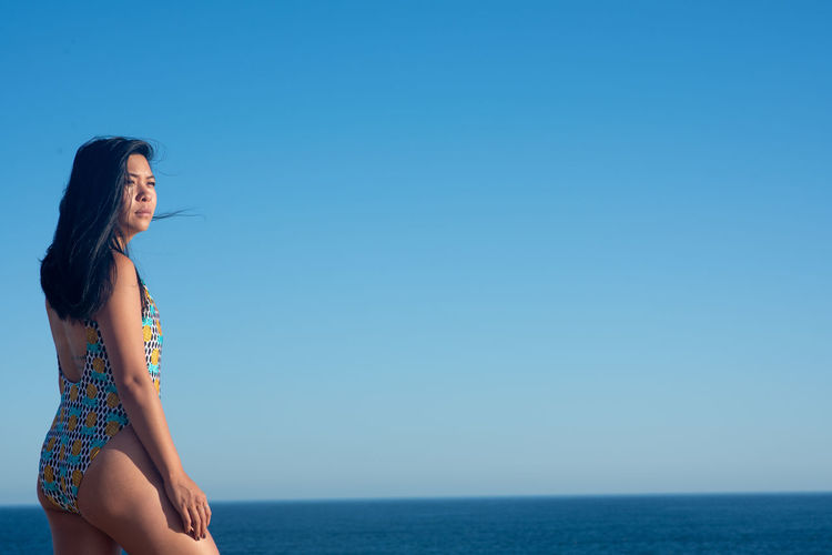 Young woman in swimwear on beach against clear sky