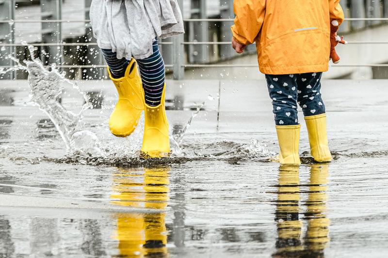 Low section of women walking on wet floor during rainy season
