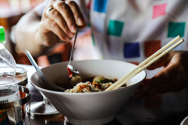 Midsection of person having food called noodles  on the table