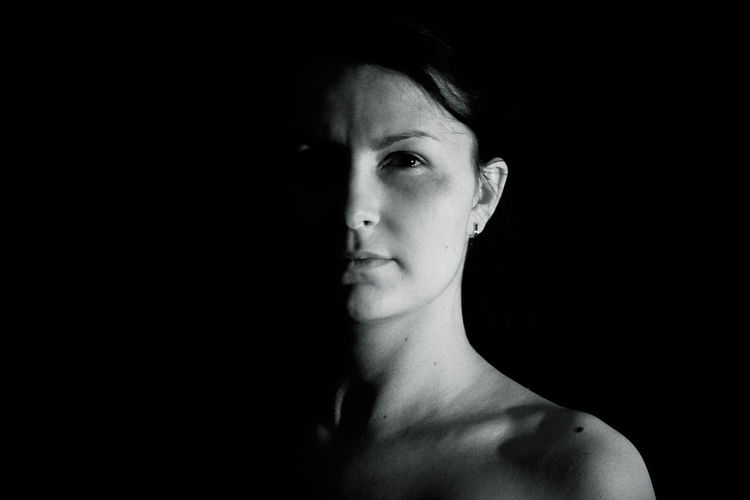 Close-up portrait of shirtless young woman standing against black background