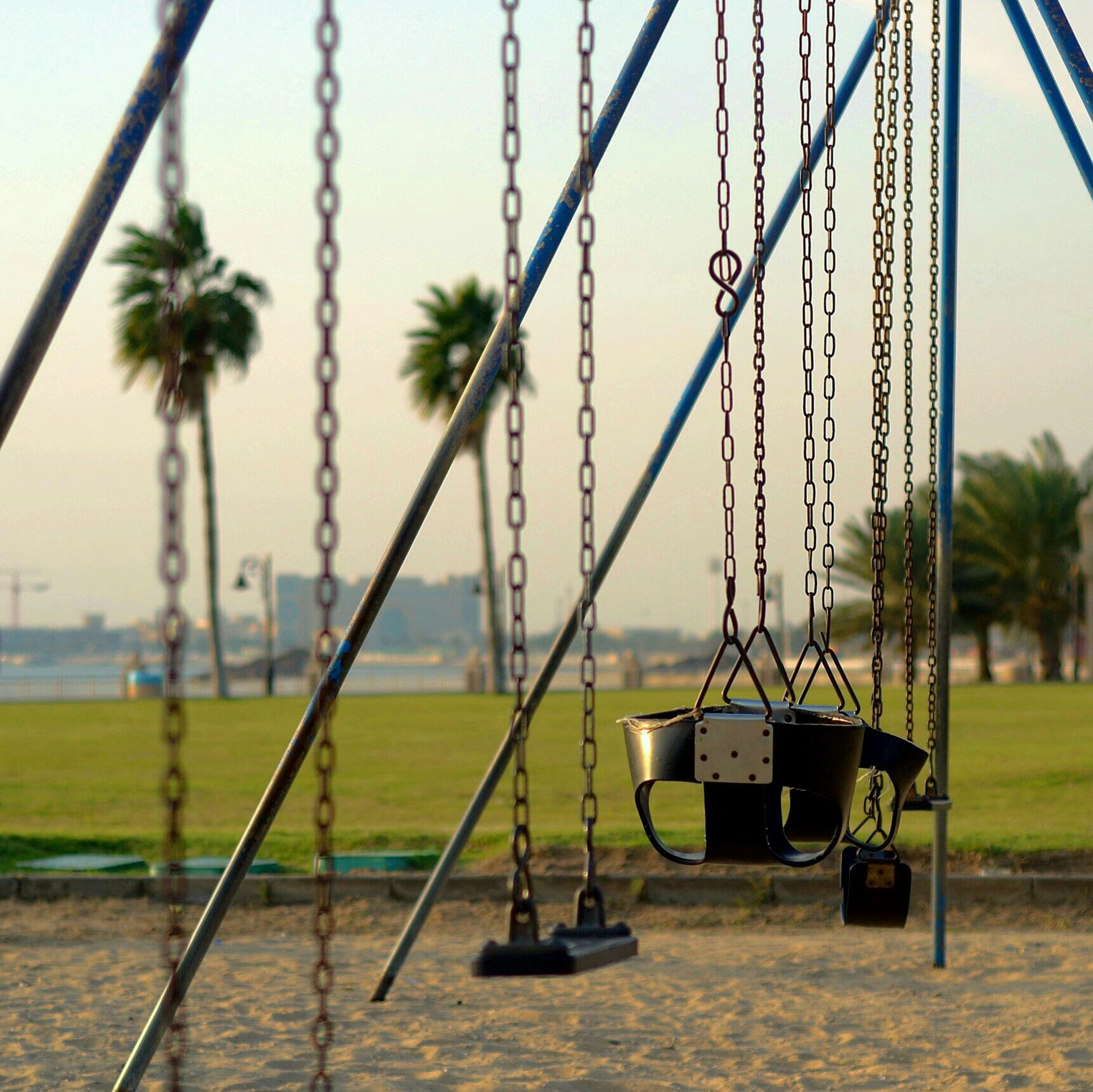 grass, sky, field, transportation, sea, focus on foreground, green color, nature, growth, water, outdoors, playground, day, swing, no people, beach, mode of transport, tranquility, tree, close-up