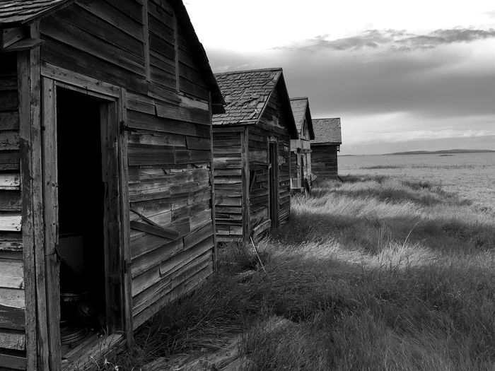 Abandoned wooden houses on grassy field against sky