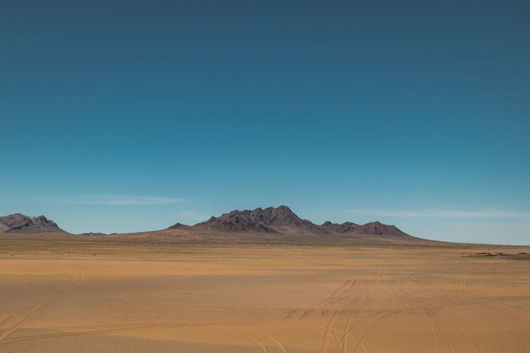 Mongolia Scenics - Nature Sky Desert Landscape Beauty In Nature Copy Space Non-urban Scene Tranquility Climate Environment Land Arid Climate Tranquil Scene Sand Blue Clear Sky Remote No People Mountain Nature Outdoors Atmospheric Salt Flat