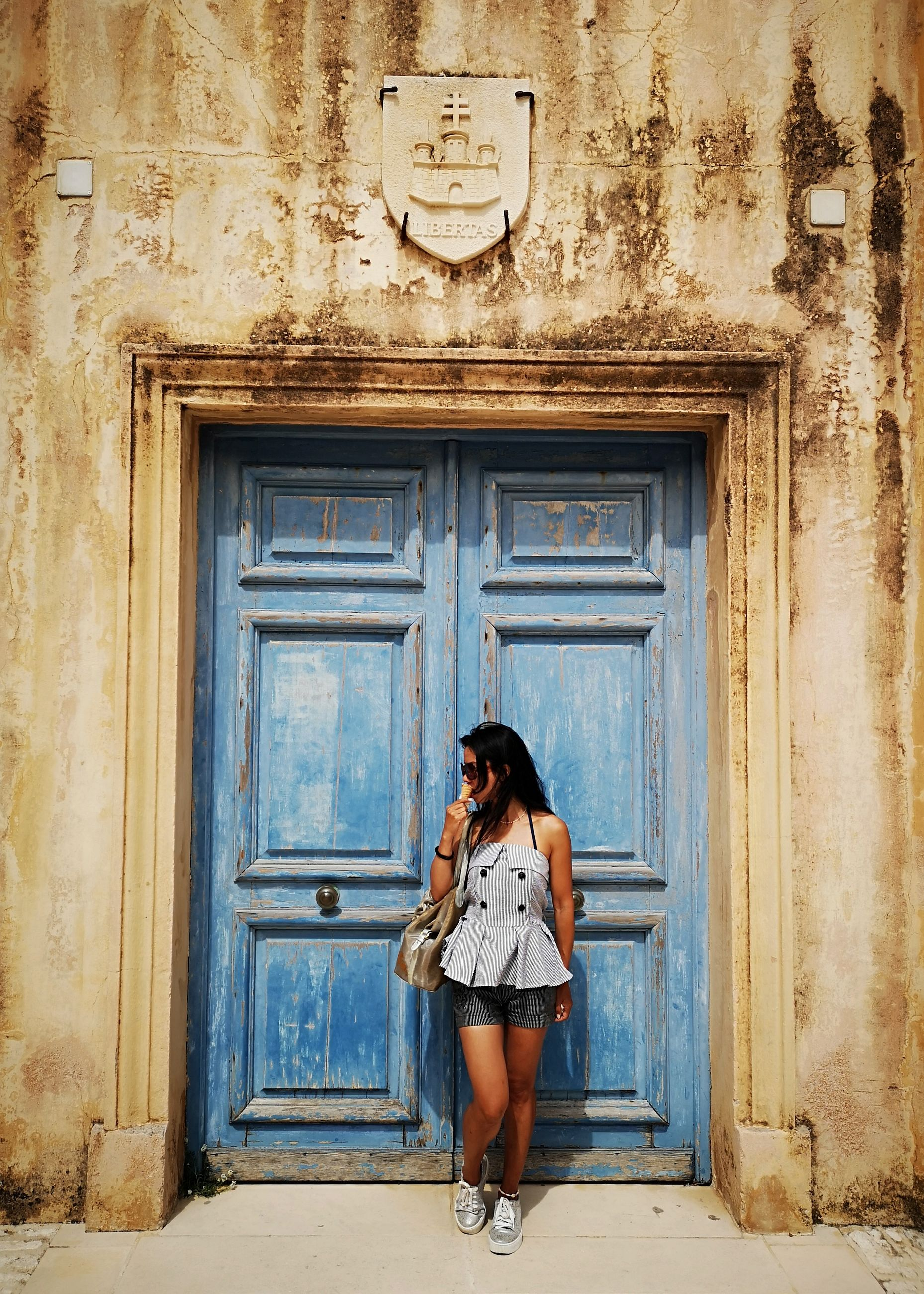 entrance, door, one person, young adult, full length, architecture, young women, standing, building exterior, closed, casual clothing, day, adult, built structure, real people, fashion, women, front view, building, beautiful woman, hairstyle, outdoors