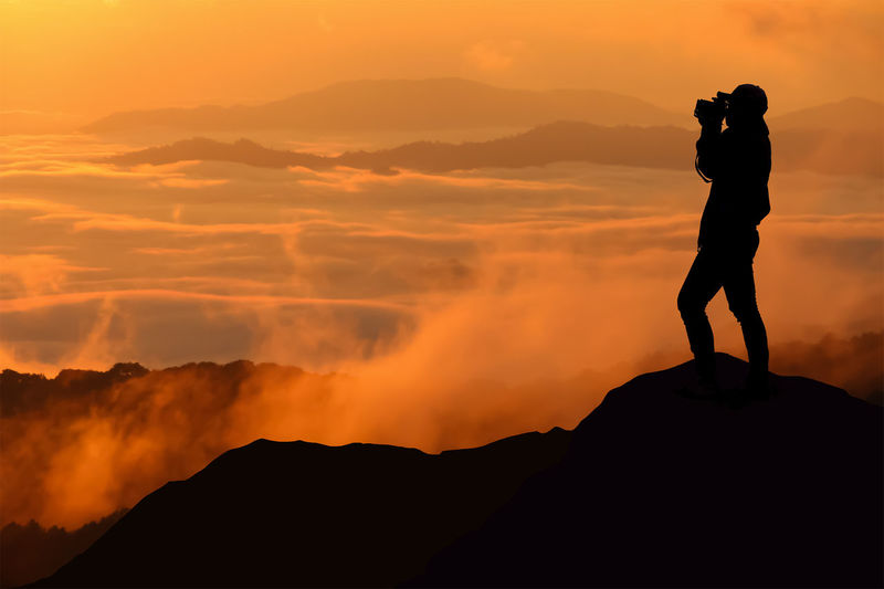 Silhouette man photographing against sky during sunset