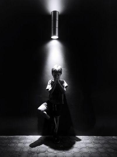 Woman sitting on wall in illuminated room