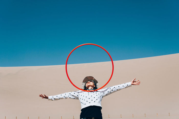Woman balancing hoop while standing against wall and clear blue sky