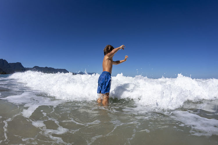 Full length of shirtless man in sea against clear blue sky