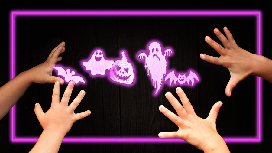 Cropped image of people hands against purple wall