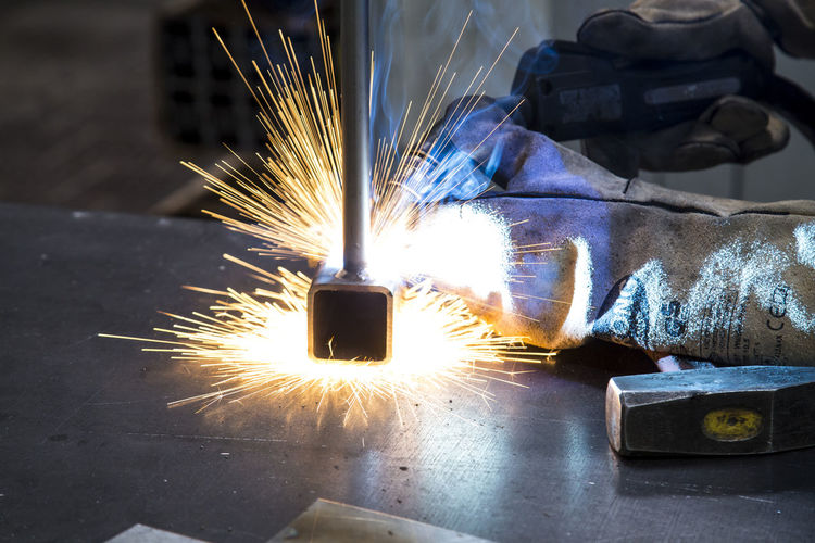 Cropped hands of welder welding at workshop