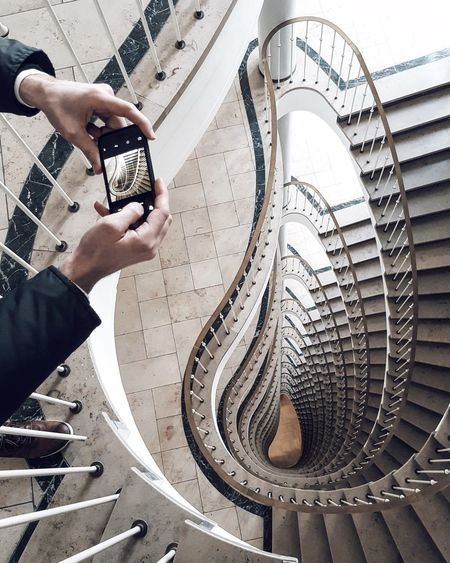 Cropped Hands Photographing Spiral Staircases Using Phone