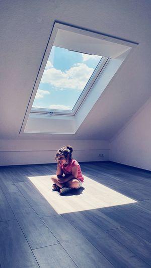 Full length of girl sitting on floor by window