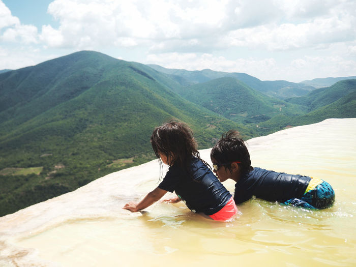 High Angle View Of Children Enjoying In Stream Against Mountains At Hierve El Agua