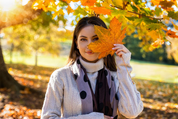 Portrait smiling of young woman with leaf standing in park during autumn