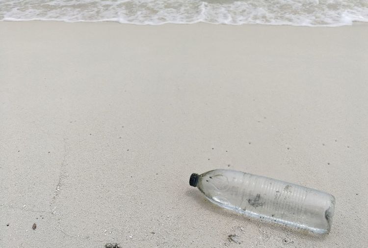High angle view of bottle on sand at beach