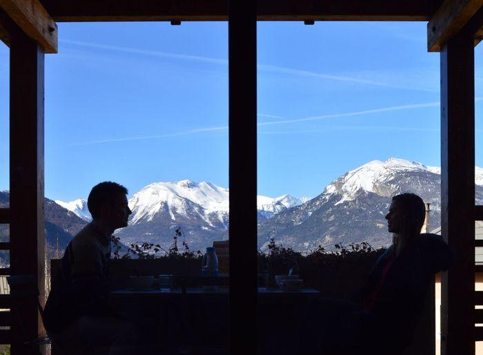 Couple enjoying breakfast at restaurant against french alps