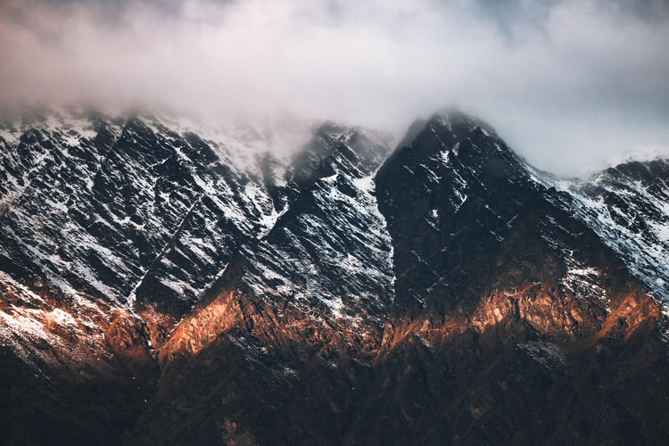 Streak of sunset light on a mountain range with clouds at the top.