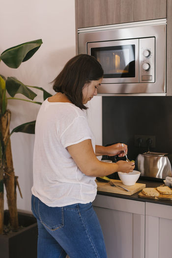 Side view of woman preparing food at home