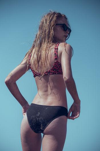 Woman in bikini standing against blue sky
