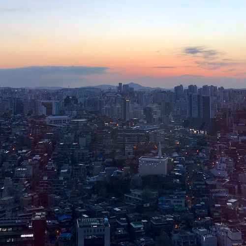 Aerial view of city against sky during sunset