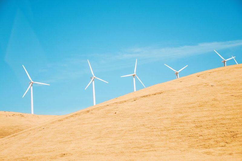 Wind turbines on desert against blue sky