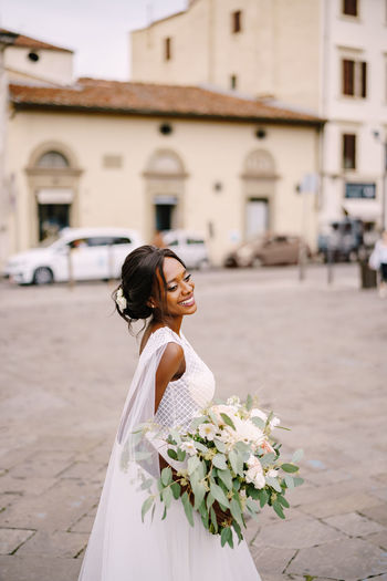Side view of bride standing with flowering plant in city