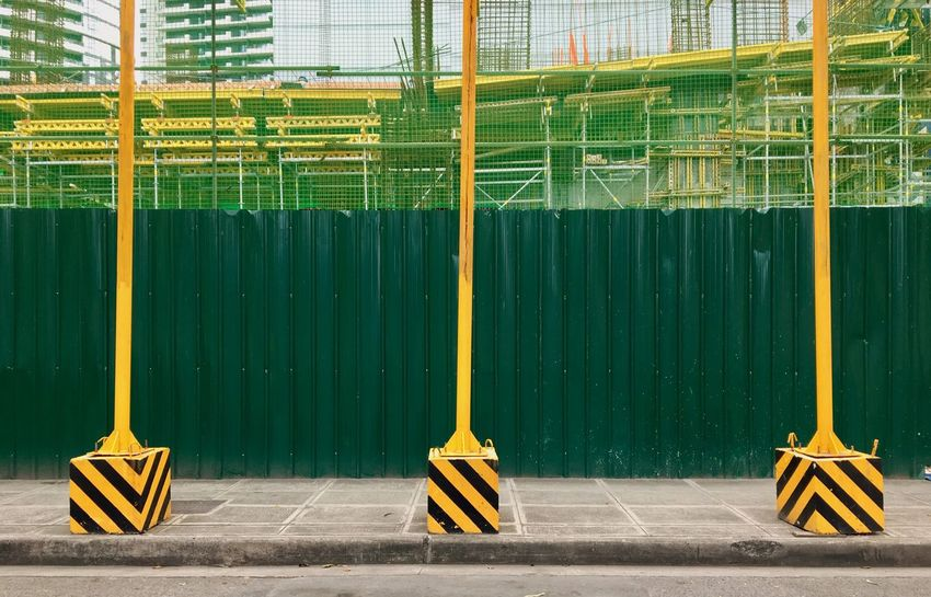 Scaffoldings, safety nets and temporary posts are installed near a construction site in Bonifacio Global City in Taguig, Metro Manila. Built Structure Yellow No People Outdoors Day Architecture Scaffolding Scaffolding Netting Ladders Walkways Pattern Geometric Nets Posts Green Wall Green Fence Philippines Manila Taguig Green Yellow Construction Site