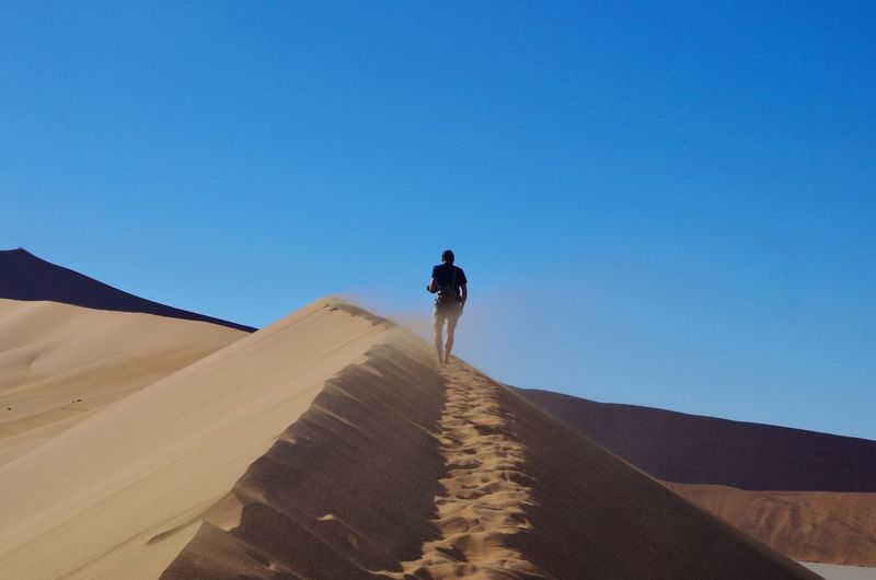 Rear view of man walking in desert against clear blue sky