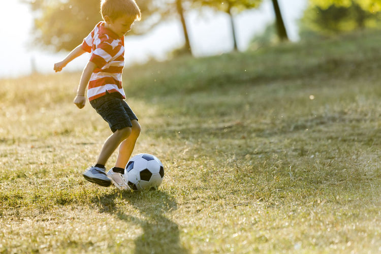 Boy playing soccer on field