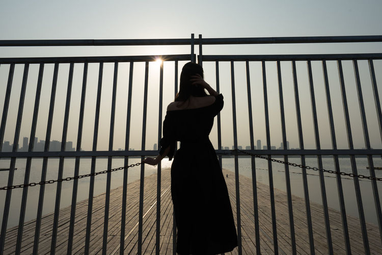 Woman standing on railing against sky