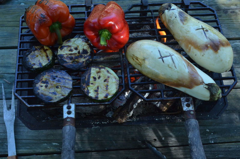 Hibachi grill with flame on white eggplant halves, red bell pepper, zucchini slices, red hot coals